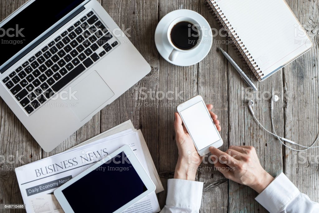 Woman using mobile phone on working table stock photo