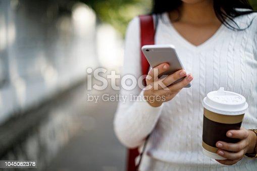 855341616istockphoto Woman using mobile phone outdoor 1045082378