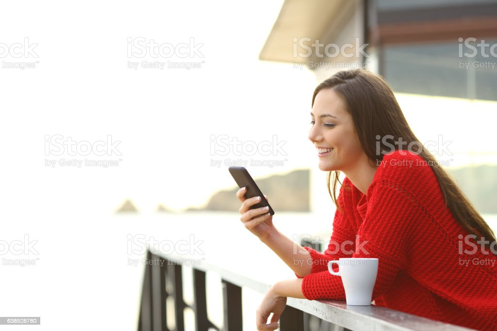 Woman using mobile phone outdoors stock photo