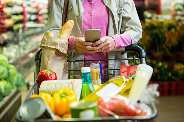Woman using mobile phone while shopping stock photo