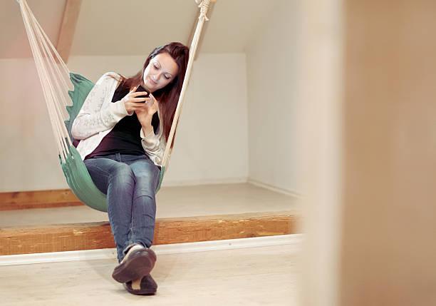 woman using mobile smart phone in her living room - divano procrastinazione foto e immagini stock