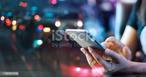 Woman using mobile smart phone in the night light colorful background