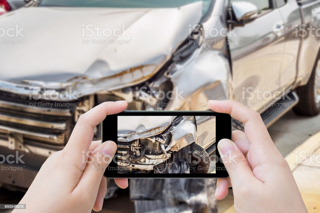 woman using mobile smartphone taking photo of car accident damaged for insurance stock photo