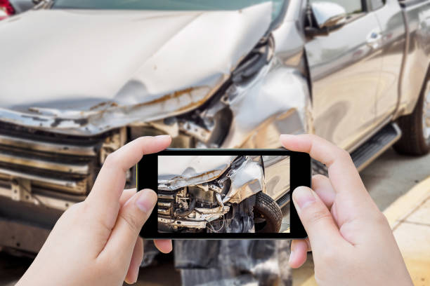 woman using mobile smartphone taking photo of car accident damaged for insurance - impaired driving stock photos and pictures