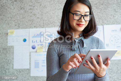 Young busy businesswoman wearing eyeglasses standing and typing on digital tablet while working at office