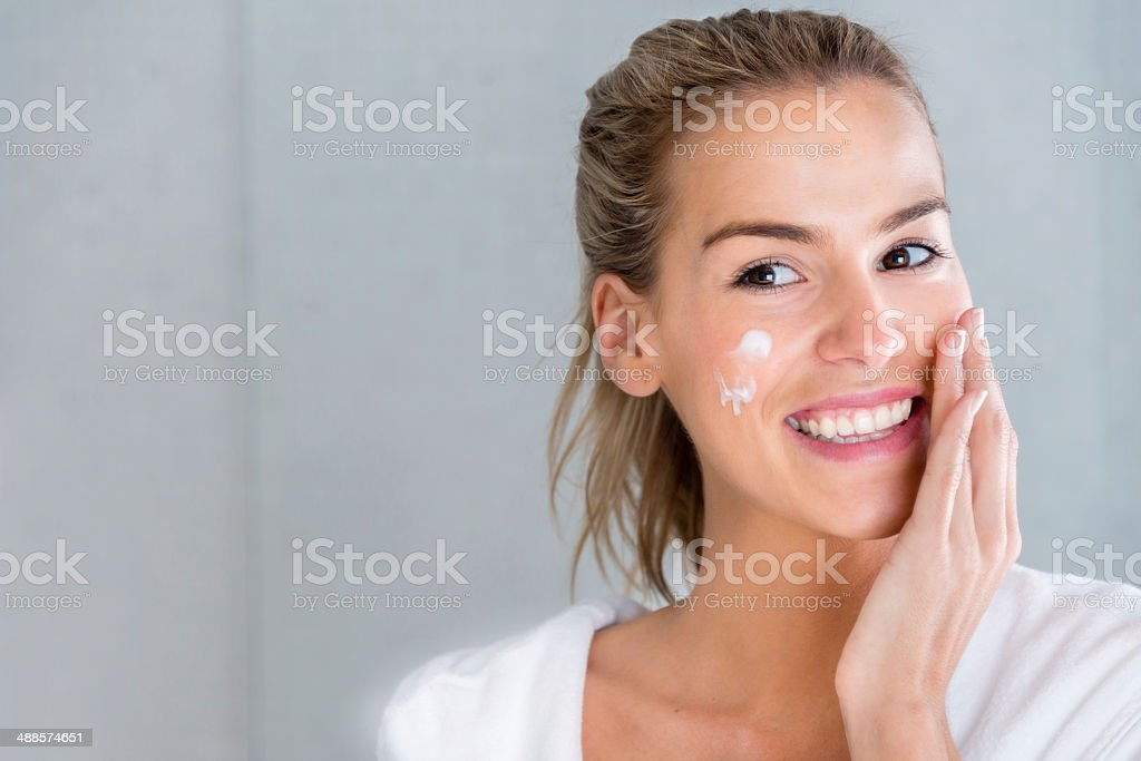 Woman using moisturising cream stock photo