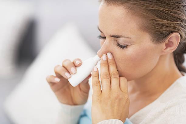 woman using nasal drops stock photo