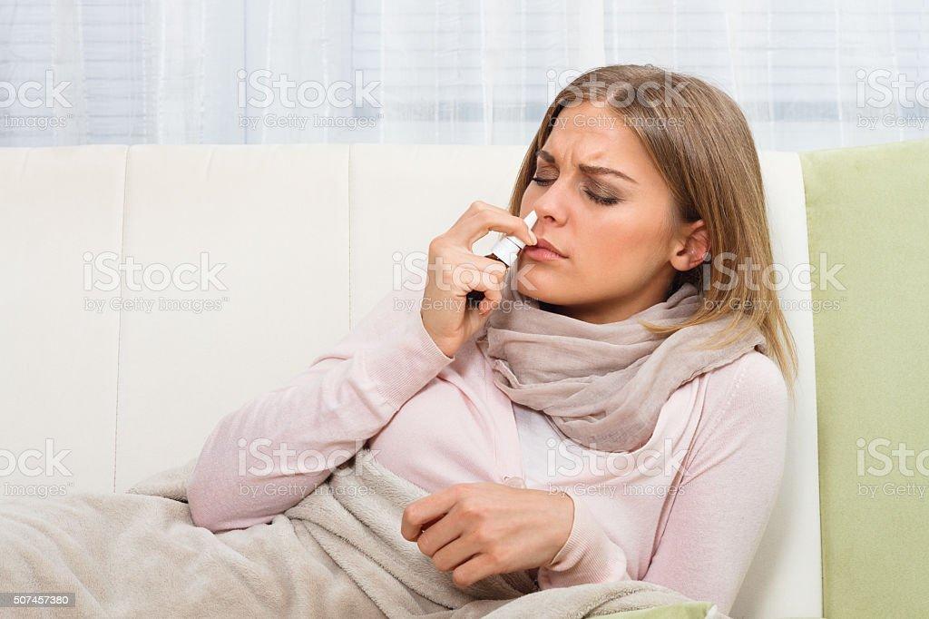 Woman using nasal spray stock photo