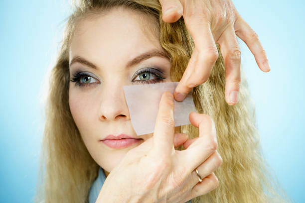 Woman using oil blotting tissues on model Professional artist fixing fashion model make up using oil blotting tissues. Cosmetic objects, beauty treatment concept. blotting paper stock pictures, royalty-free photos & images