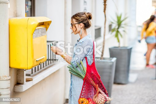 istock Woman using old mailbox outdoors 846082602