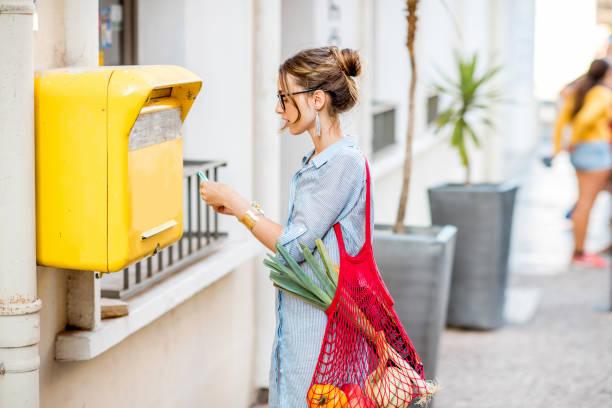 mujer usando buzón antiguo al aire libre - postal worker fotografías e imágenes de stock