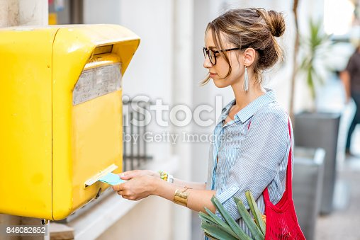 istock Woman using old mailbox outdoors 846082652