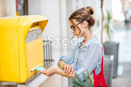istock Woman using old mailbox outdoors 846082670