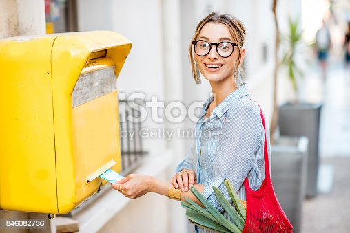 istock Woman using old mailbox outdoors 846082736