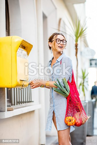 istock Woman using old mailbox outdoors 846082916