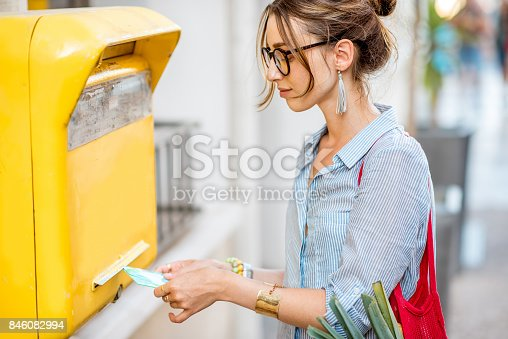 istock Woman using old mailbox outdoors 846082994