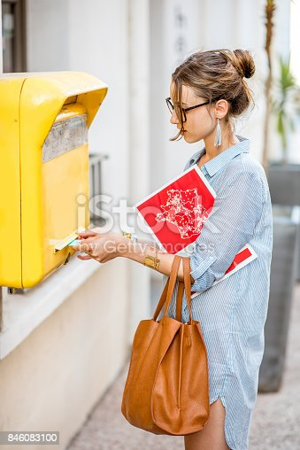 istock Woman using old mailbox outdoors 846083100