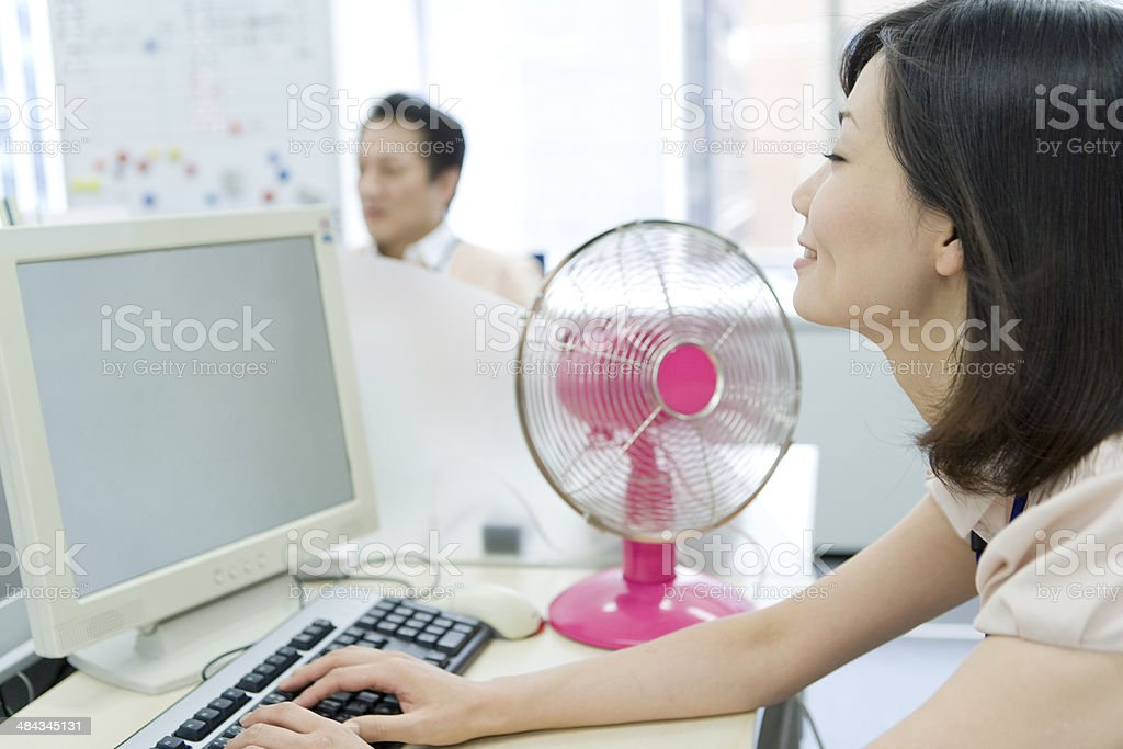 Woman using PC on desk with an electric fan stock photo
