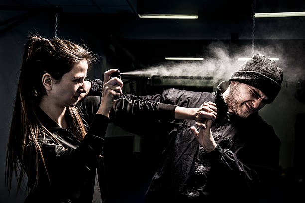 Woman using pepper spray for self defense against attacker The young woman is defending herself from an attacker. Mixed pair demonstrates using of a pepper spray for self defense. The attacker - a young man, wearing a black jacket and knit cap. self defense stock pictures, royalty-free photos & images
