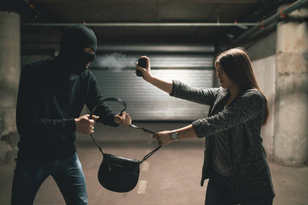 Woman using pepper spray for self defense against thief stock photo