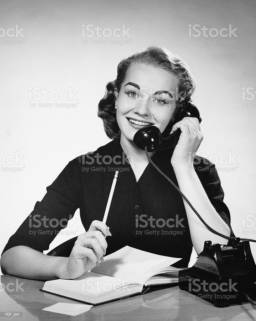 Woman using phone and holding pencil royalty-free stock photo