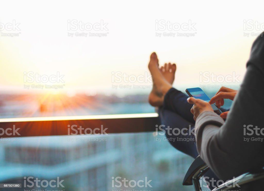 Woman using phone and relaxing at end of the day with feet up stock photo