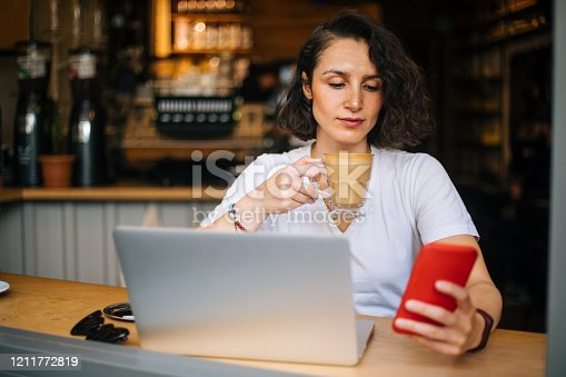 Woman using phone at cafe