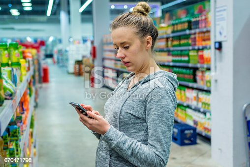 sale, shopping, consumerism and people concept - happy young pregnant brown hair woman with smartphone choosing and buying food in market,