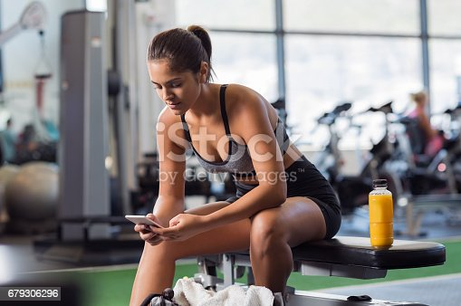 istock Woman using phone at gym 679306296