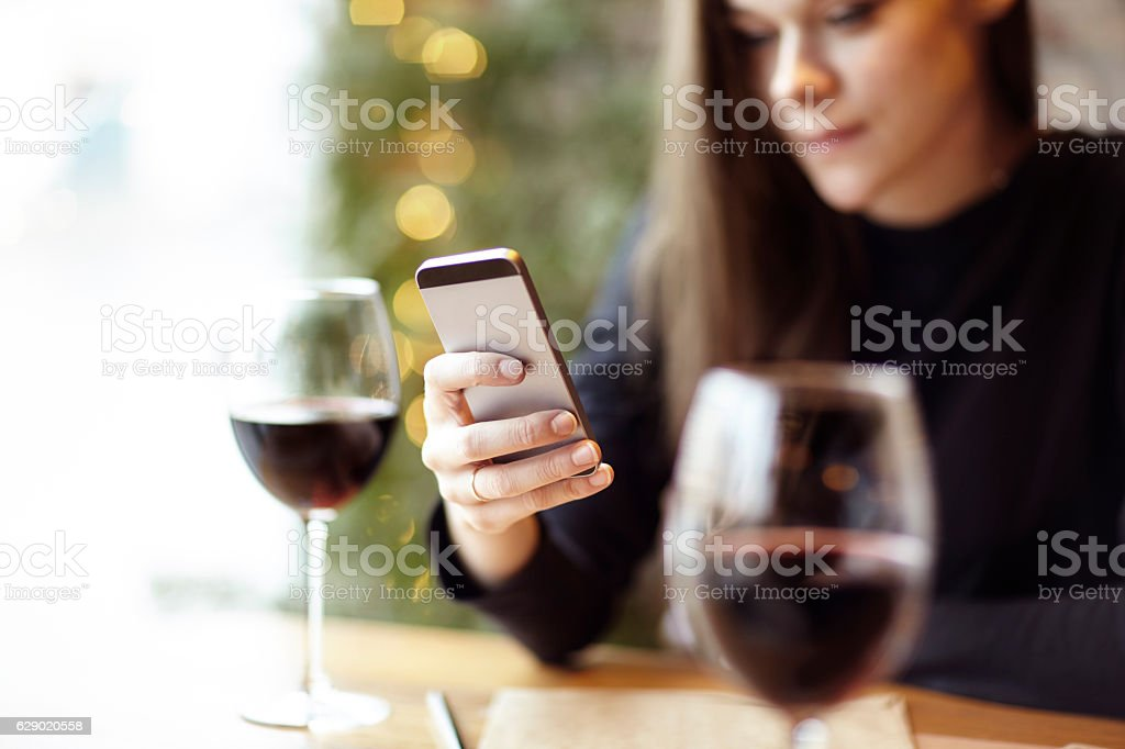 Woman using phone during lunch. Drinking glass of red wine in a cafe....