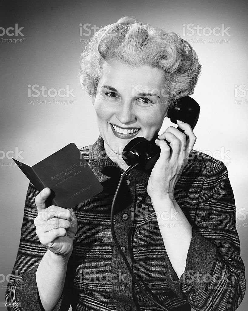 Woman using phone, holding small book in one hand royalty-free stock photo