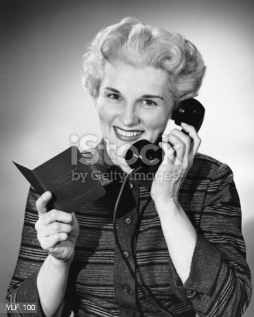 Woman Using Phone Holding Small Book In One Hand Stock Photo & More Pictures of 1950-1959