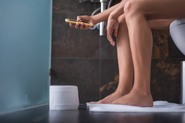 vrouw met behulp van telefoon in toilet - cell phone toilet stockfoto's en -beelden
