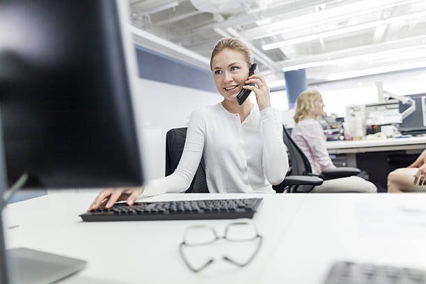 Woman using phone in office stock photo