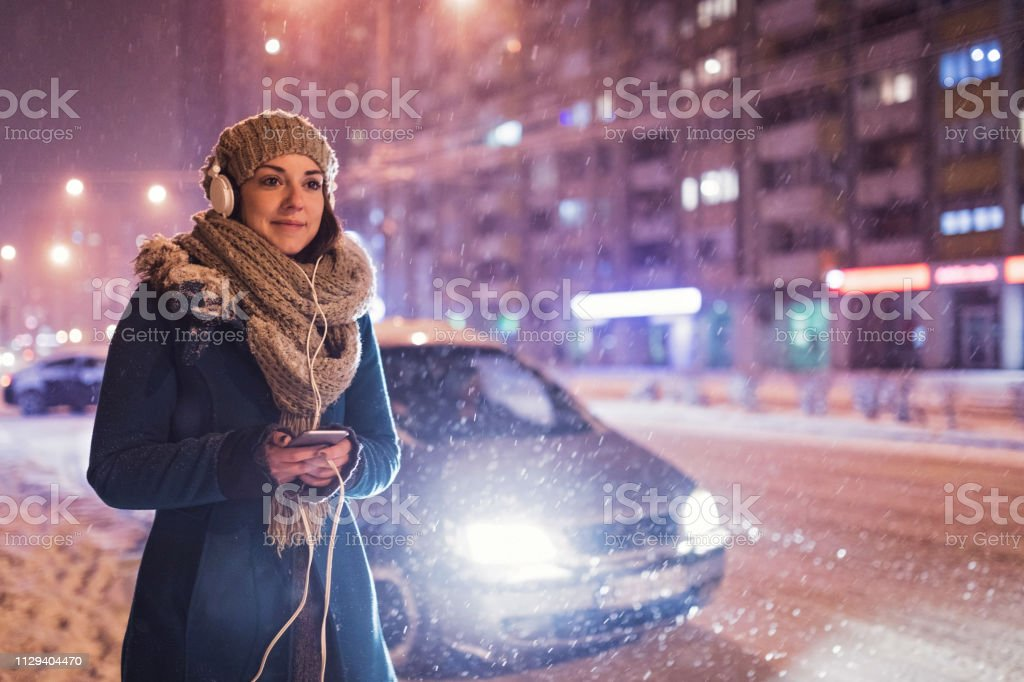 Woman using phone in snowy outdoors stock photo