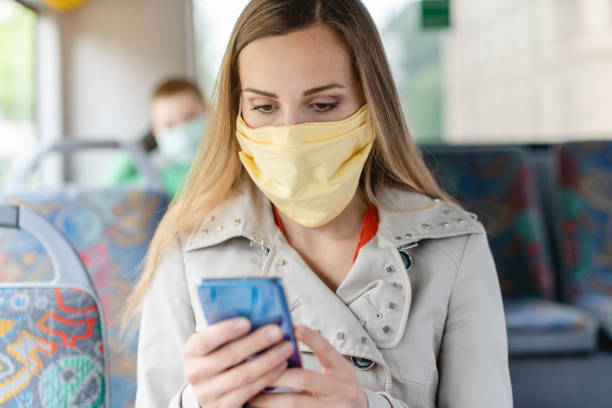 Woman using phone in the bus wearing a face mask stock photo