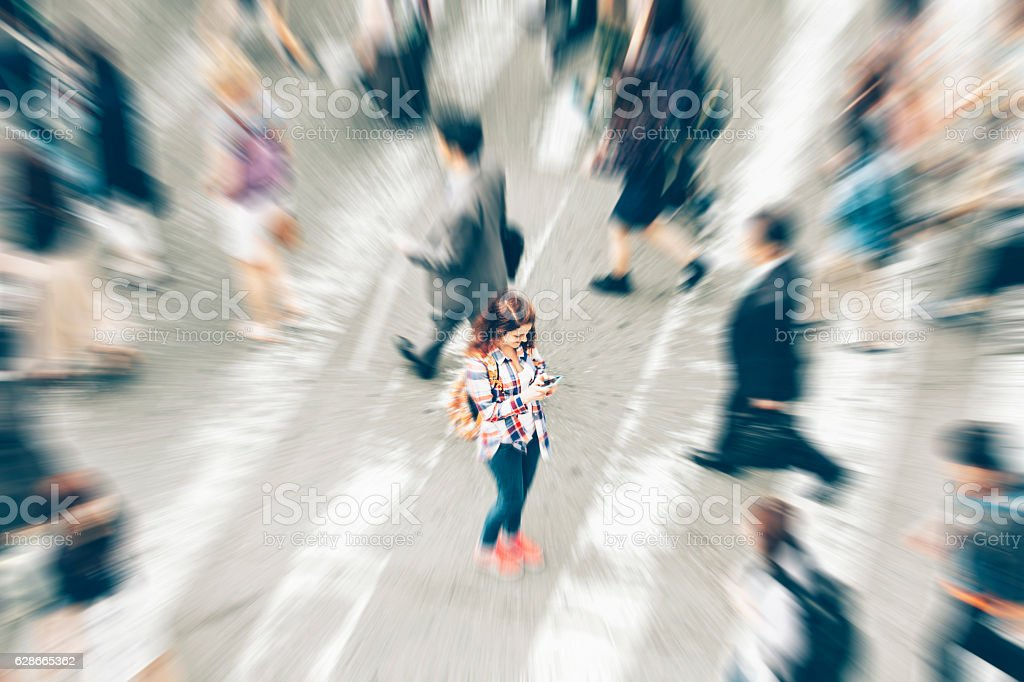 Woman using phone in the middle of crowd crossing street stock photo