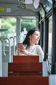 istock Woman using phone in tram, Hong Kong City 1277296477
