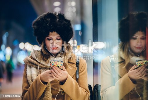 Young caucasian beautiful woman texting on her phone at a city street.