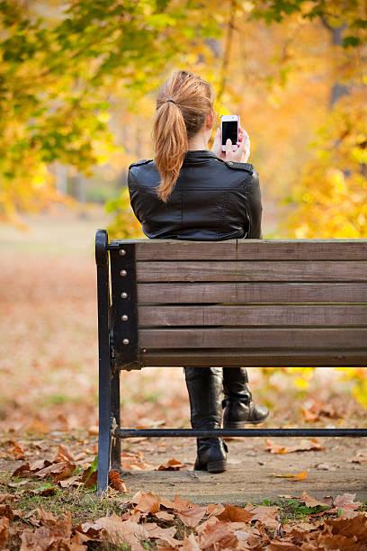frau mit telefon im freien am schönen herbst tag - sitzbank schuhe stock-fotos und bilder