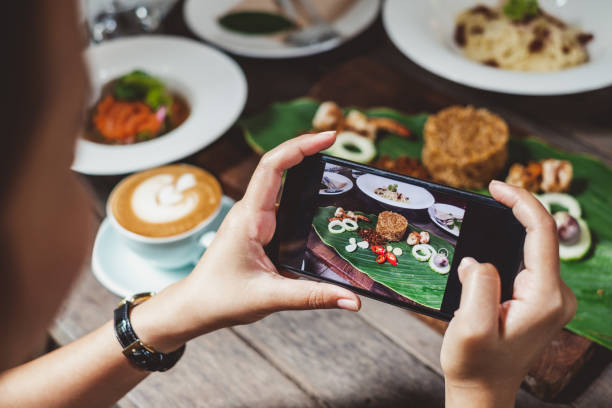 woman using phone taking photo for food dinner and lunch meal on table - foodie stock photos and pictures