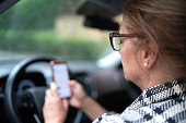 istock Woman using phone while driving 1150174887