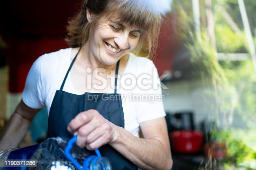 Woman using plastic bottle at kitchen