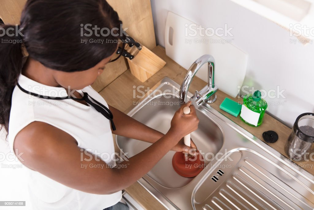 Woman Using Plunger In Blocked Kitchen Sink Stock Photo