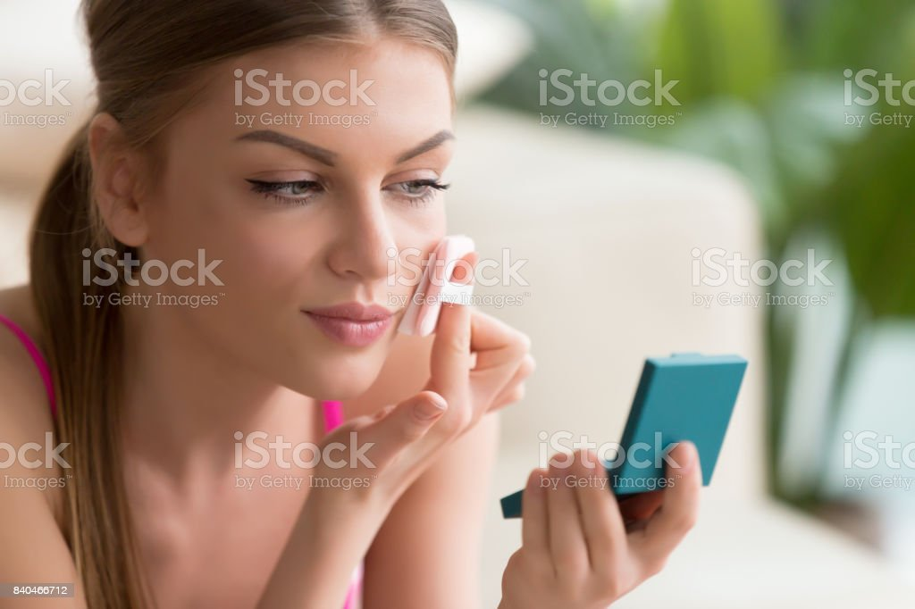 Woman using powder box with mirror and puff – zdjęcie