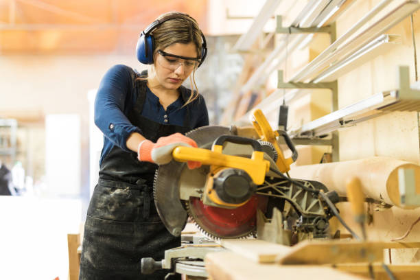 woman using power tools in a woodshop - carpenter stock photos and pictures