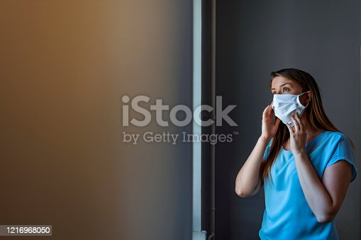 COVID-19 Pandemic Corona virus Woman Home Isolation Auto Quarantine Wearing Face Mask Protective against SARS-CoV-2. Girl with mask on face against Corona virus Disease 2020 looking through the window.