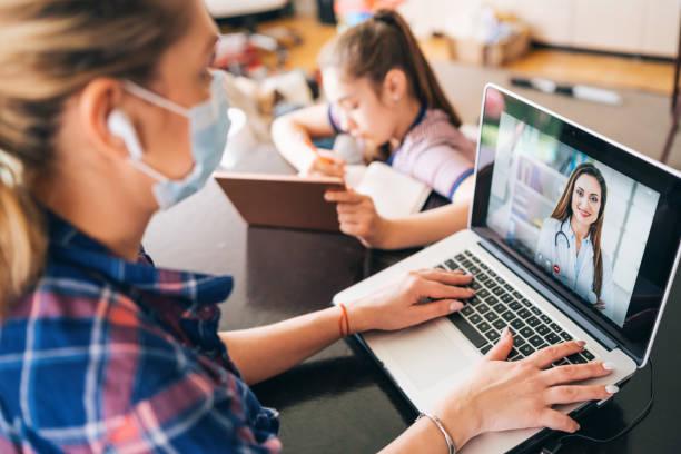 Frau mit Schutzmaske im Gespräch mit Arzt auf Laptop Isolierung zu Hause für Virus – Foto