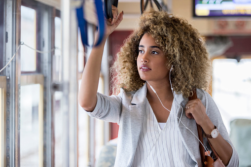 Confident young female commuter rides to work on a bus or train. She is holding a handgrip.
