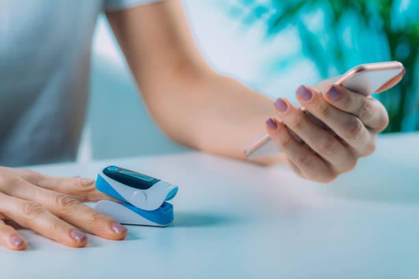 Frau mit Pulsoximeter und Smart Phone, Messung der Sauerstoffsättigung – Foto